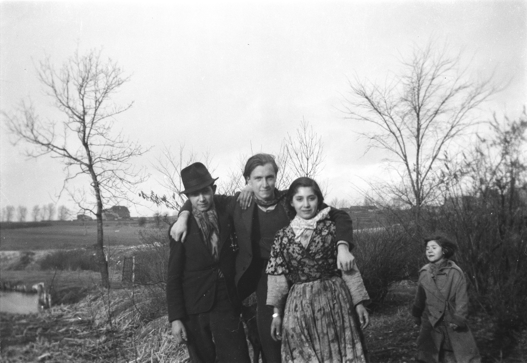 Jan Yoors (center) poses with arms around Romani (Gypsy) friends, as a child looks on.