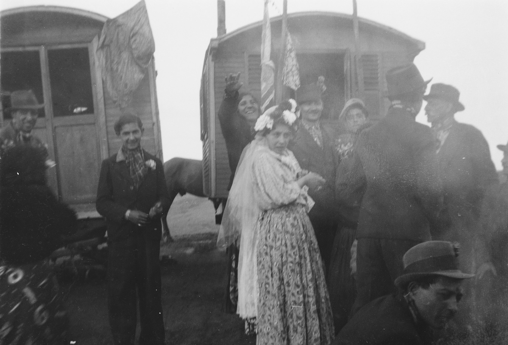 A Romani (Gypsy) woman wearing a long white veil poses with a group in a front of caravans decorated with flags and banners (possibly a wedding).