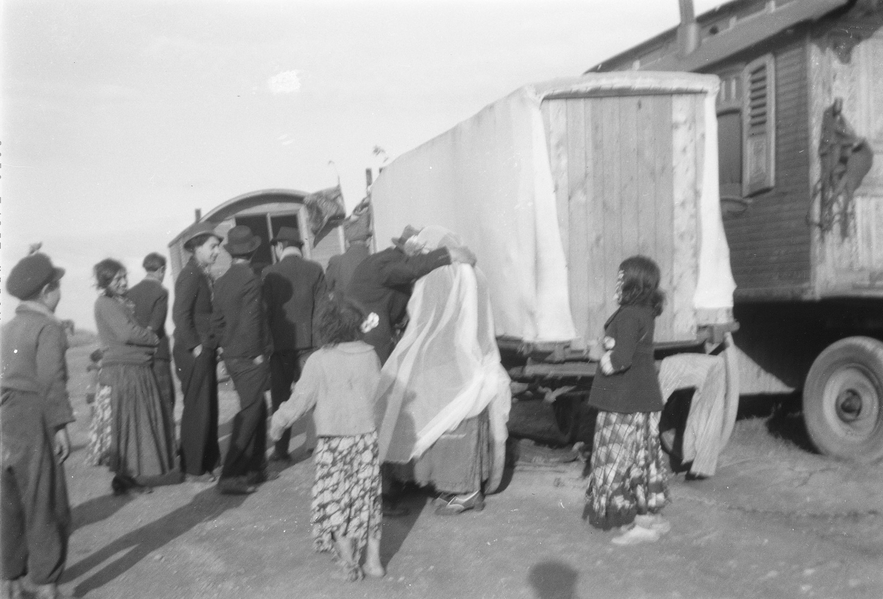 A group of Roma (Gypsies) gather alongside a caravan, possibly during a wedding.  One woman wears a long white veil.