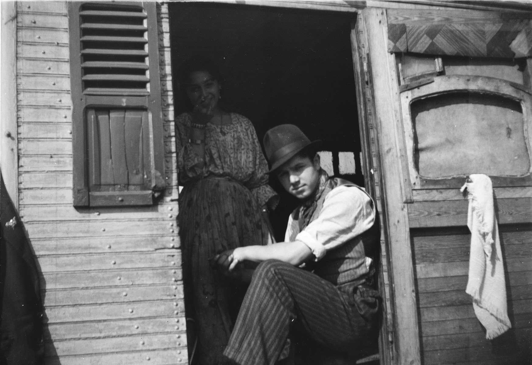 A Romani (Gypsy) couple poses in the doorway of their caravan.  Pictured in the door is Yayal (last name unknown).