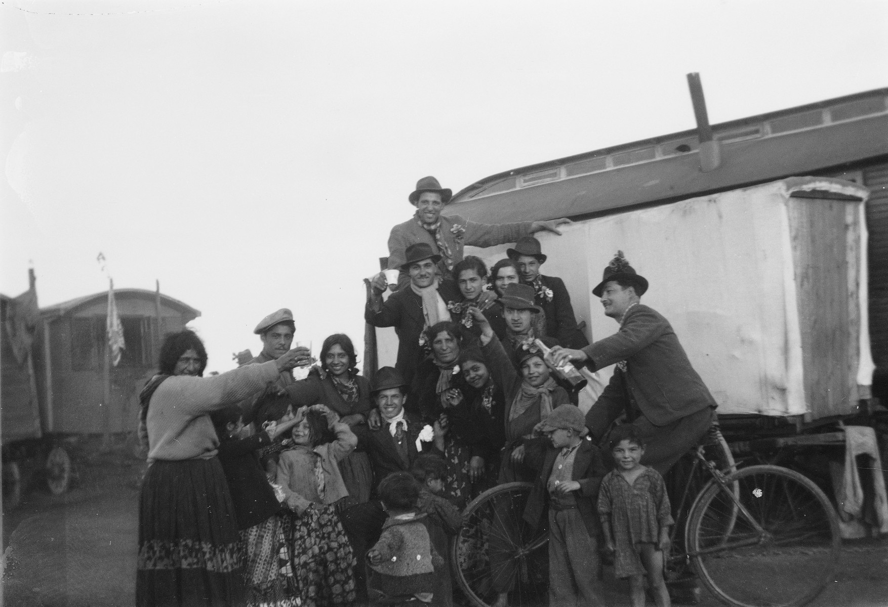 A Romani (Gypsy) group celebrates (possibly a wedding), as several raise their drinks in a toast.