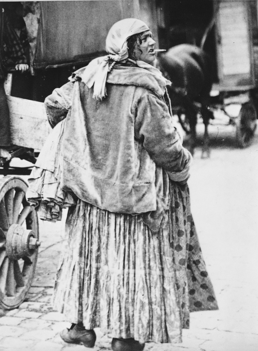 "A Romani (Gypsy) woman identified as ""Liza, a Tshurara woman,"" stands on a city street next to a caravan."