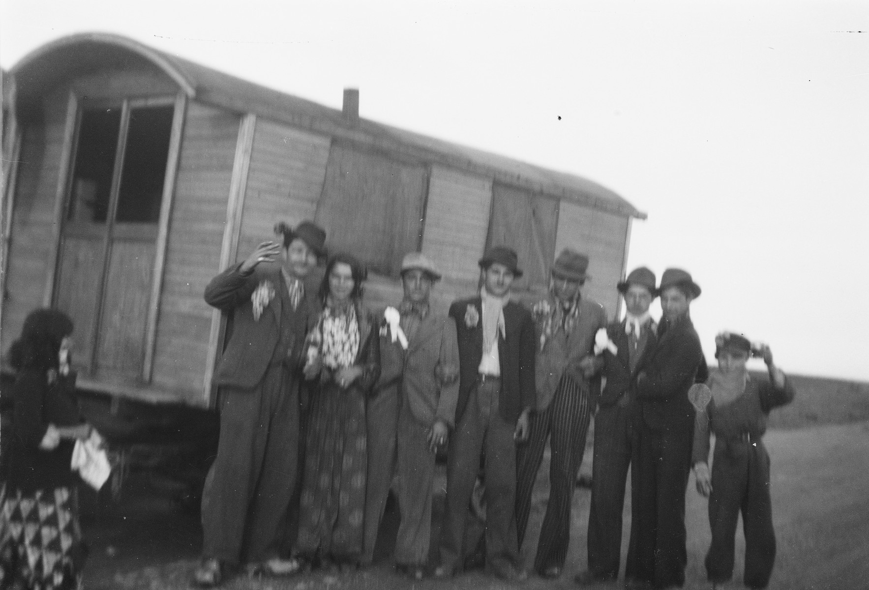 A group of Roma (Gypsies) poses alongside a caravan, possibly during a wedding.
