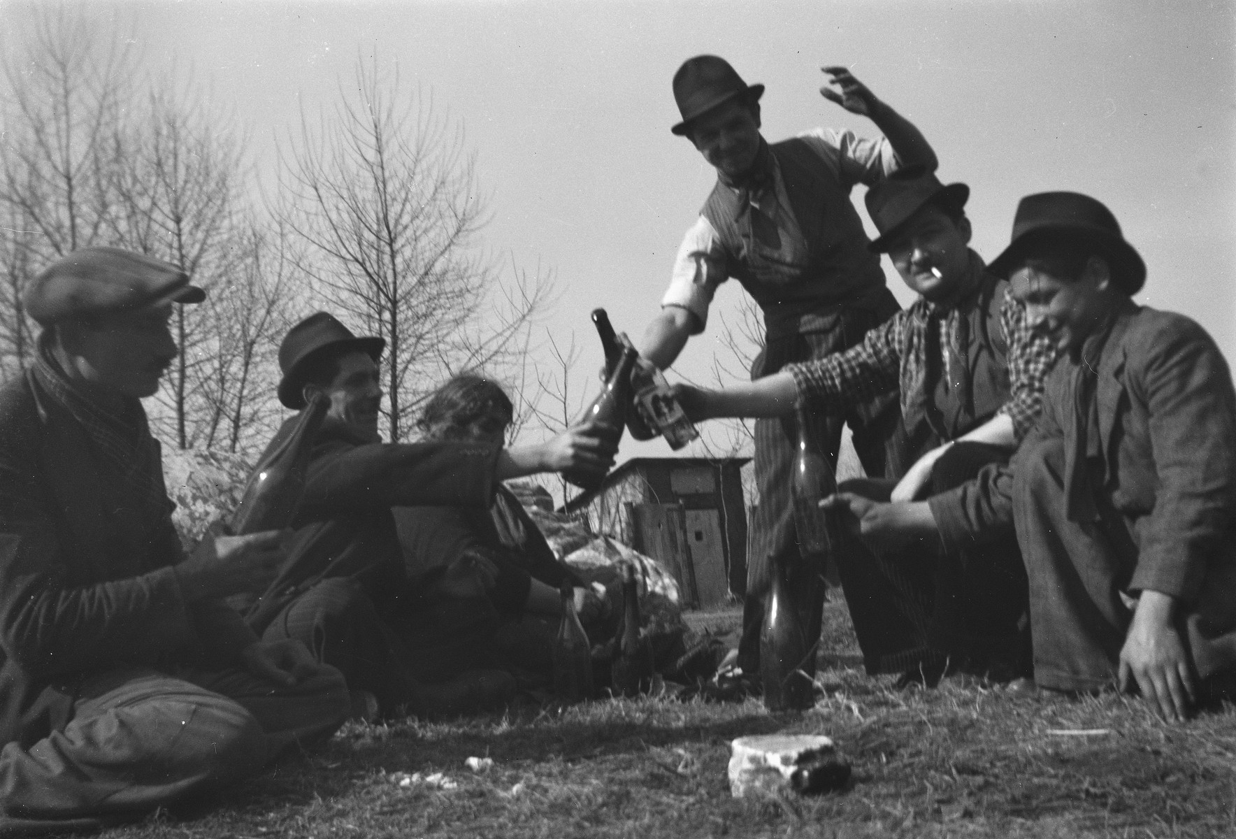 A group of Roma (Gypsy) men lift bottles in a toast.