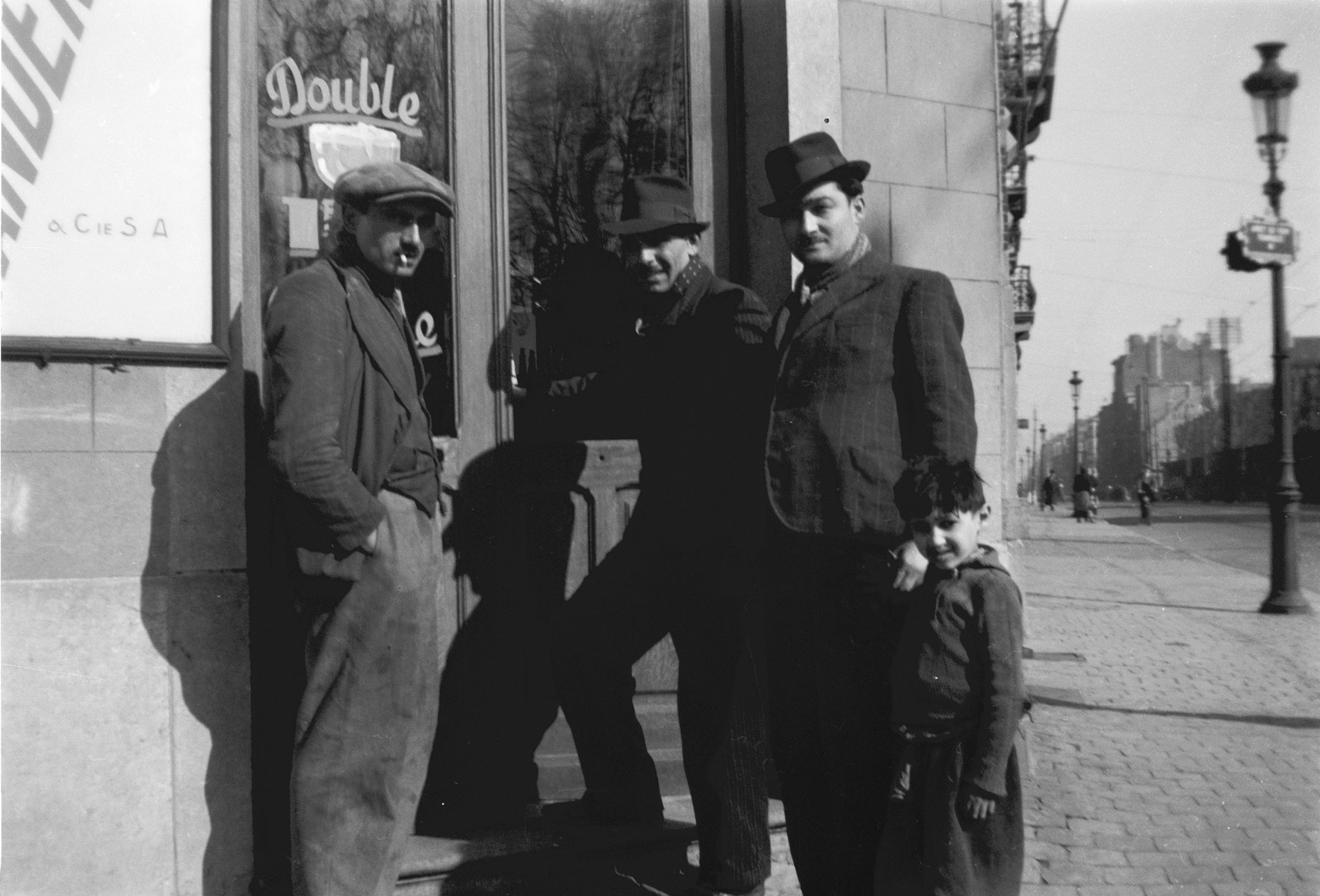 Three Romani men and a young boy stand outside the front door of a bar in Brussels.