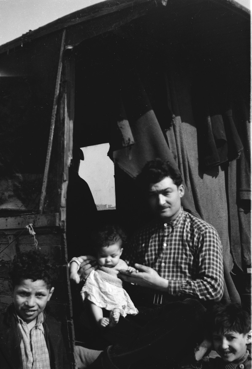 A Romani (Gypsy) man holding a baby sits in the doorway of his caravan, with two young boys on either side.