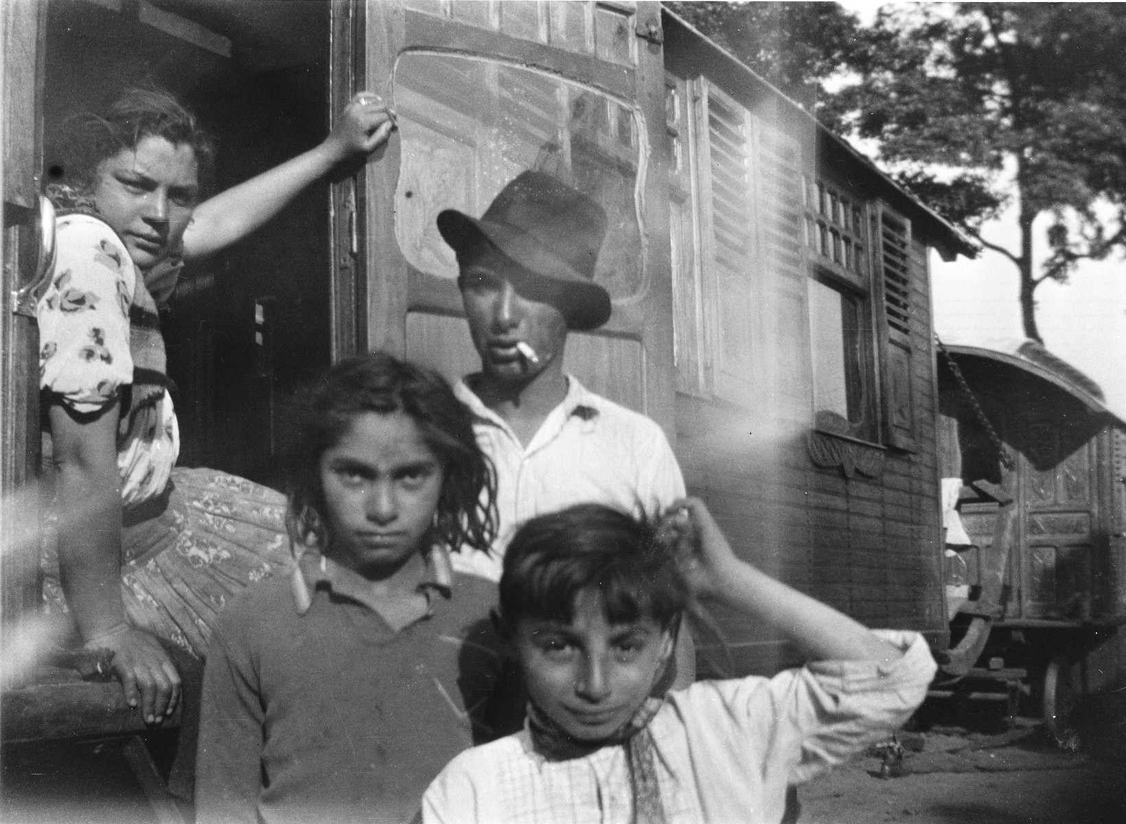 A Romani (Gypsy) family.  A boy, a girl, and a young man stand outside the caravan, with a young woman seated in the doorway.