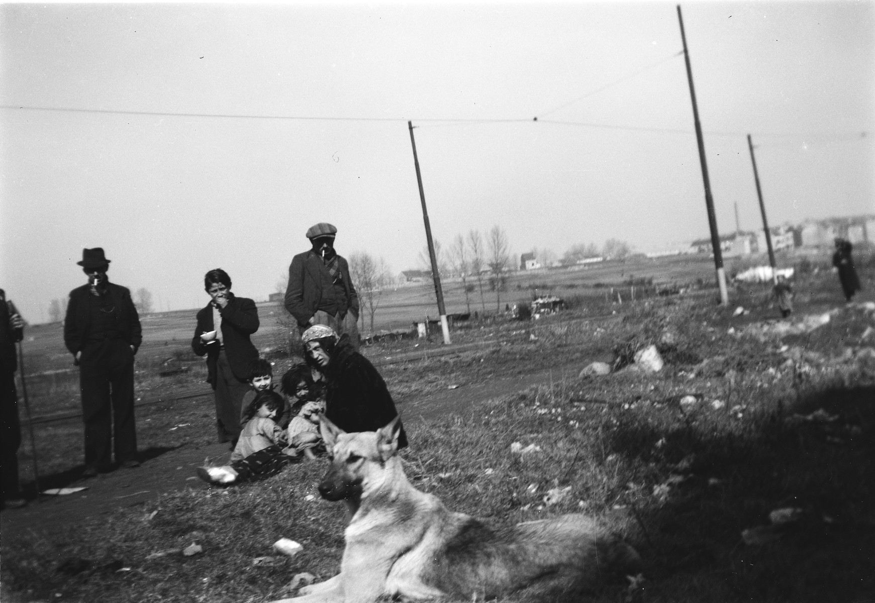 A Romani (Gypsy) family poses outdoors , while a dog sits in the foreground.