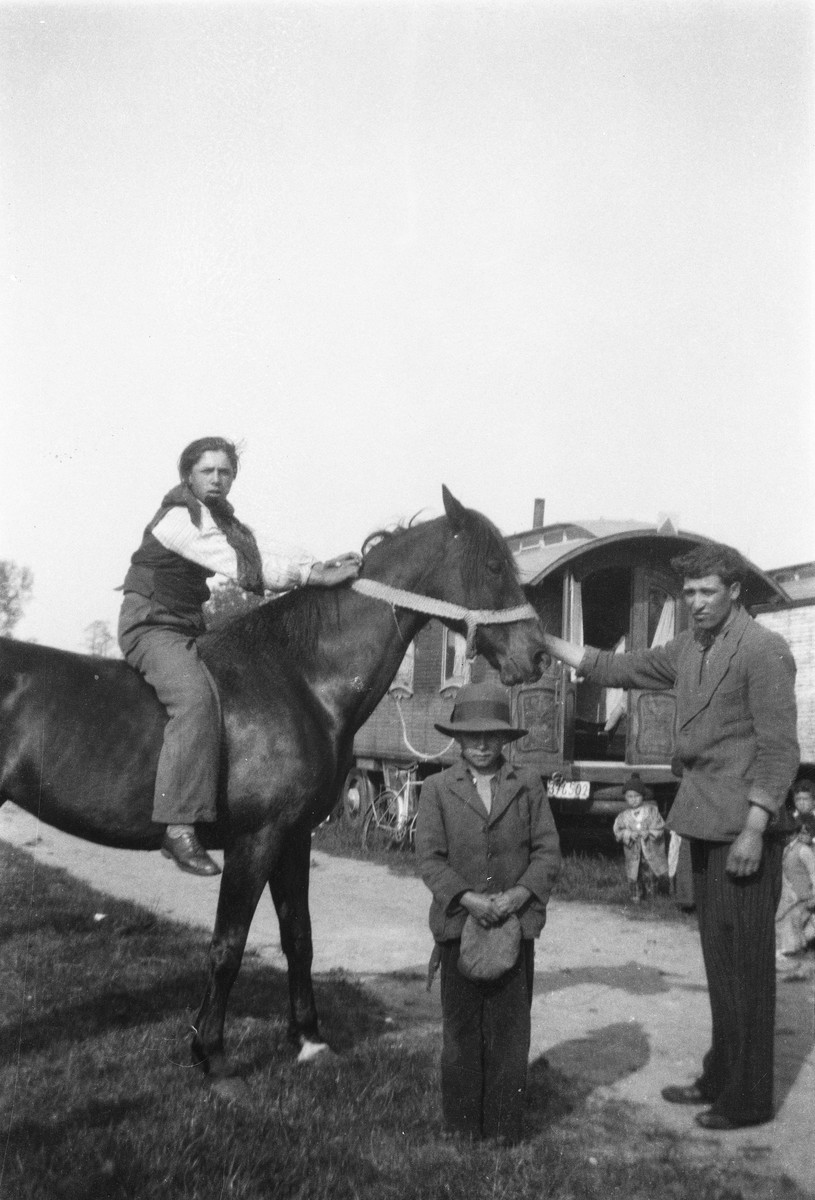 A Roma (Gypsy) man holds a horse, as another man sits astride it and a young boy stands in front.