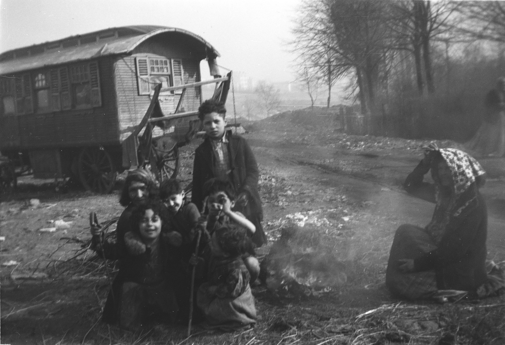 A group of  Romani (Gypsy) children and a Romani woman sit on the ground next to a camp fire.