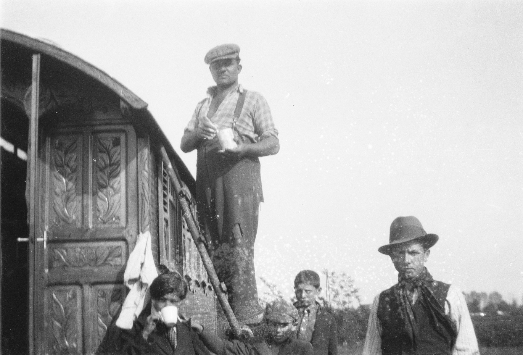 "A Romani man standing on a ladder works on his caravan. Three young boys and another man stand below.  The caption in ""The Heroic Present"" reads, ""Laetshi, Putzina, Nanosh, Kore, and Tshukurka (standing in caravan).  Europe, 1930s.""  Pictured on the right is Yayal (last name unknown)."