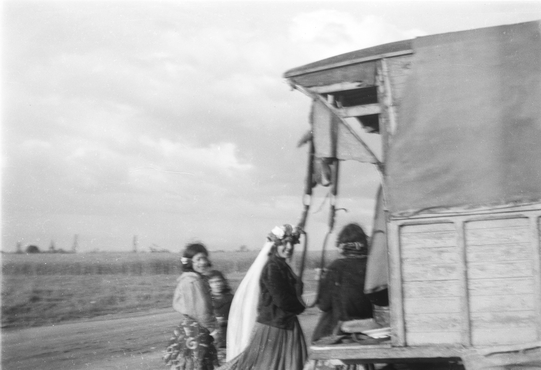 Several Romani (Gypsy) women, one wearing a long white head scarf, gather near a caravan (possibly as part of a wedding celebration).
