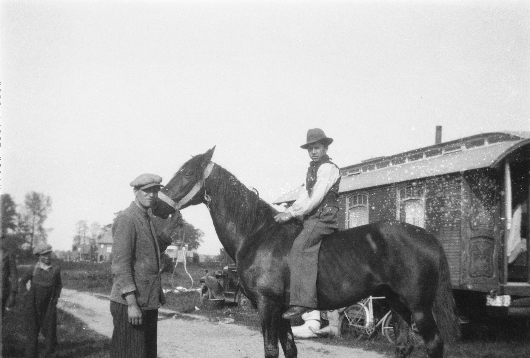 A Roma (Gypsy) man holds a horse as Yayal (last name unknown), another man is seated astride.