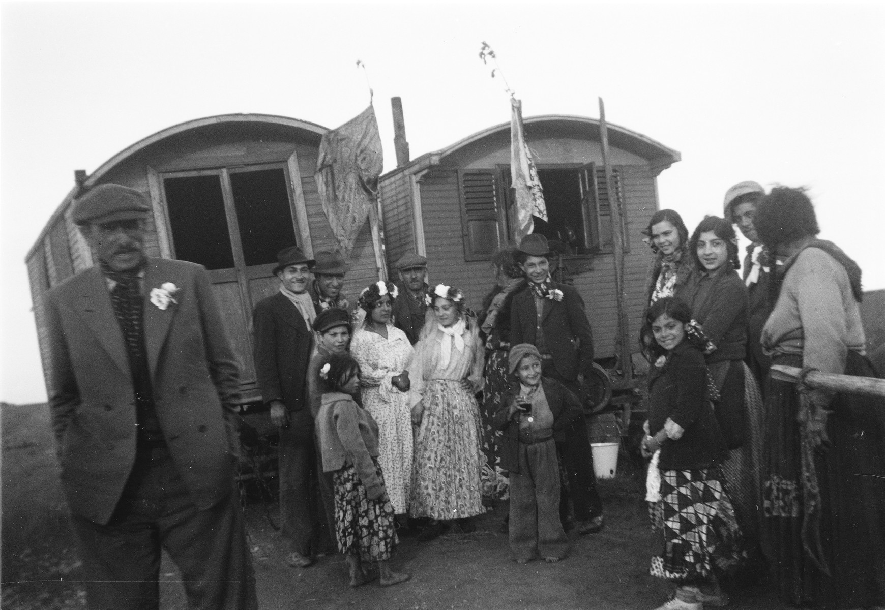 A Romani wedding party poses in front of two caravans.
