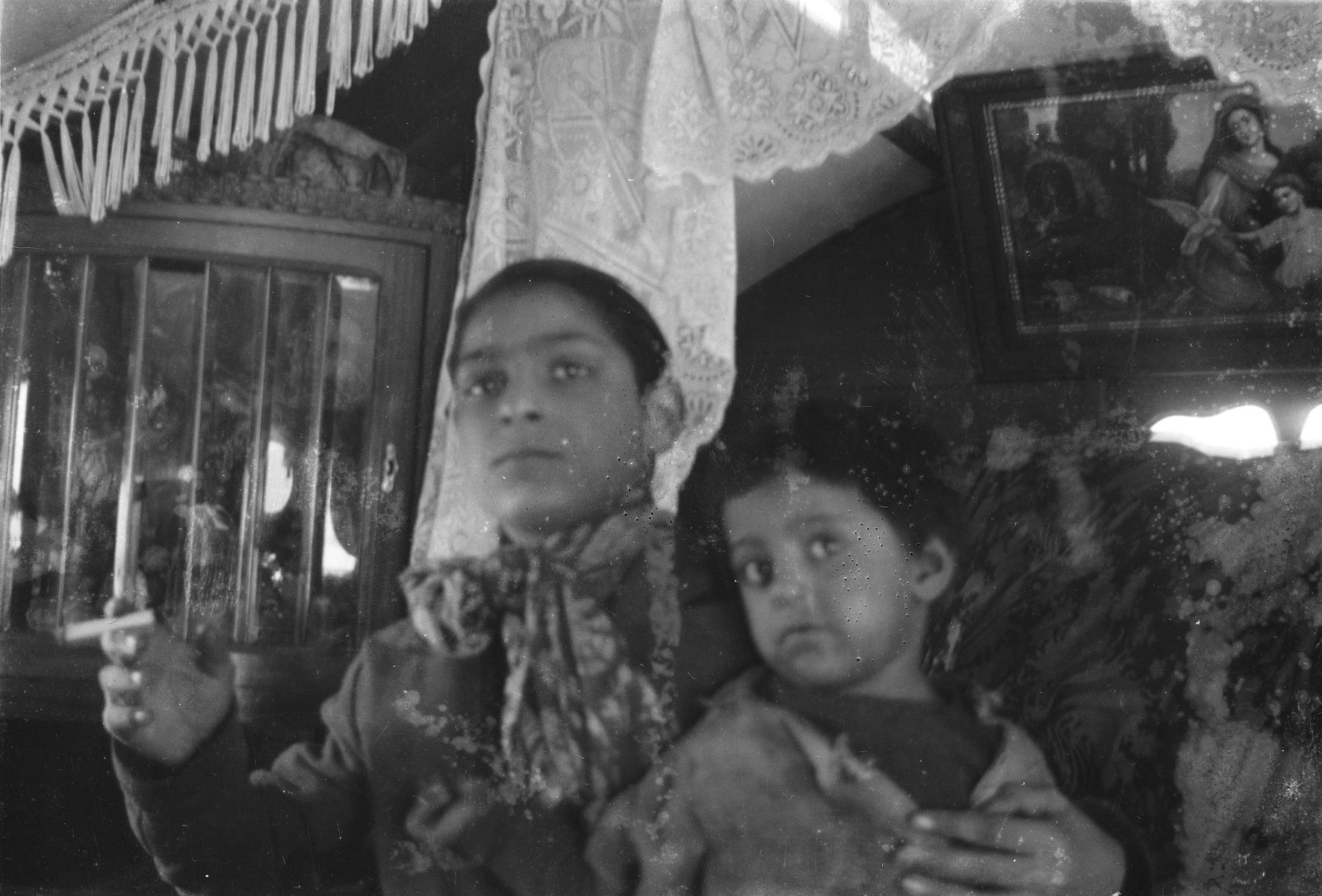 Portrait of a Roma youth holding a child, probably seated inside a caravan.
