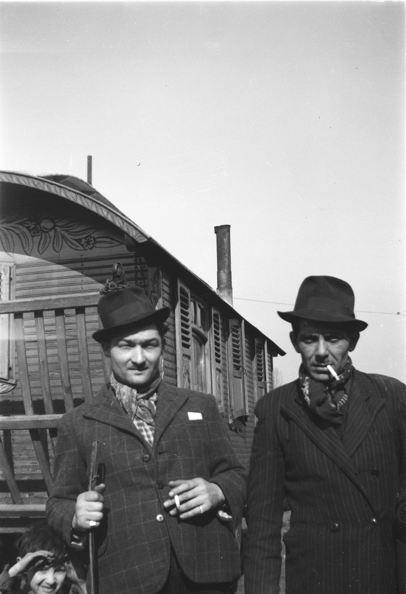 Two Romani (Gypsy) men pose in front of a caravan.