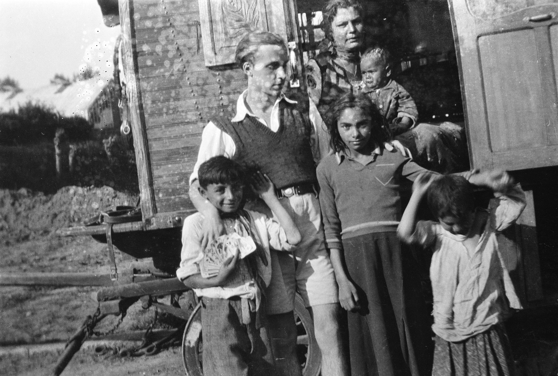 """A Roma (Gypsy) family poses around the doorway of their caravan with Jan Yoors (left, back).  The caption in """"The Heroic Present"""" reads, """"Belgium, 1930s.  Yoors is standing second from the left with his arms around Zurka, the son of Yoors' adoptive uncle, Tshukurka, and Keya, his adoptive sister."""""""