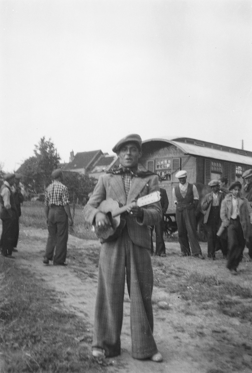 A Roma (Gypsy) musician plays a stringed instrument; behind him a group of men gather near their caravan.