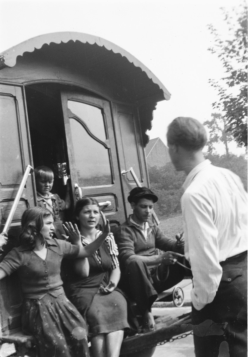 Jan Yoors (with back to the camera) visits with a group of Romani (Gypsy) youth seated at the doorway of their caravan.
