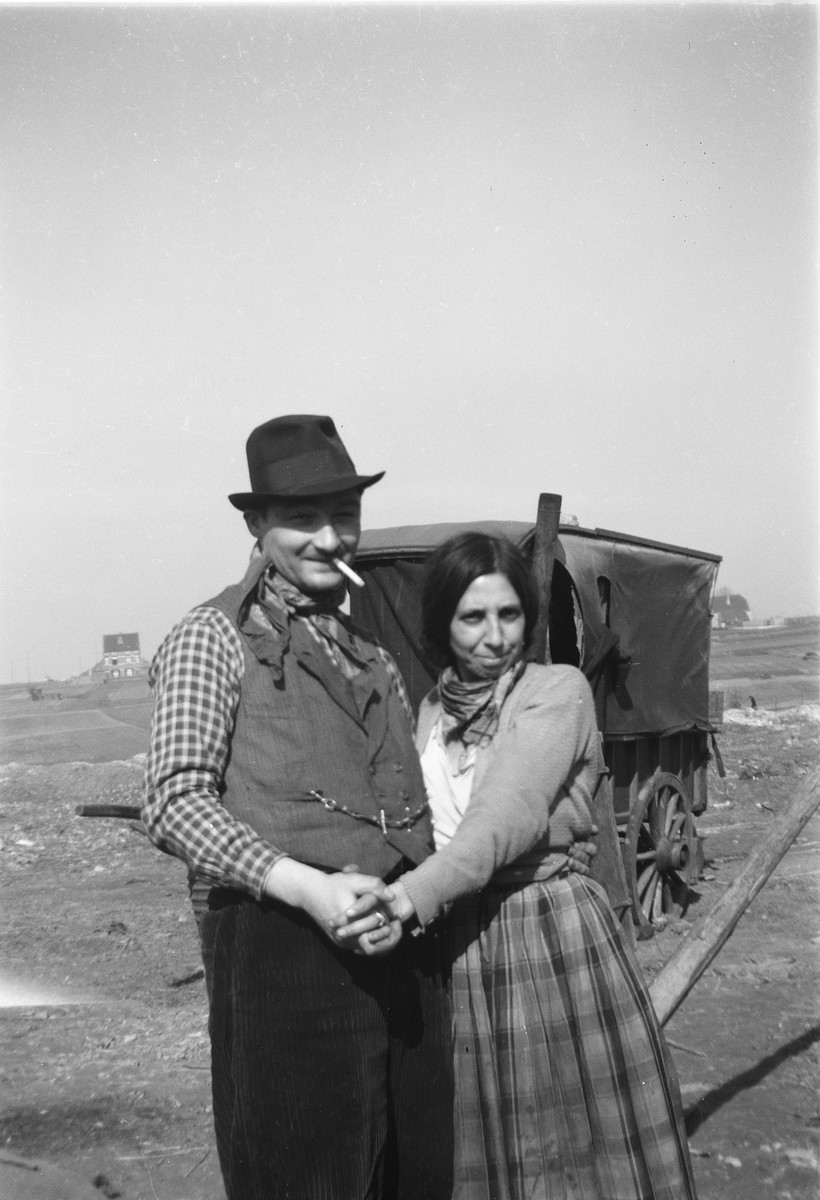 A smiling Romani (Gypsy) couple poses with hands clasped.