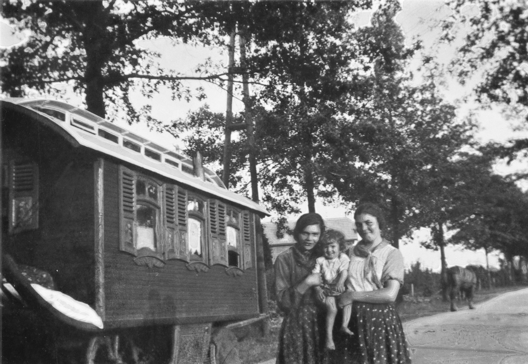 Two smiling Romani (Gypsy) women stand on a road next to a caravan, holding a baby.