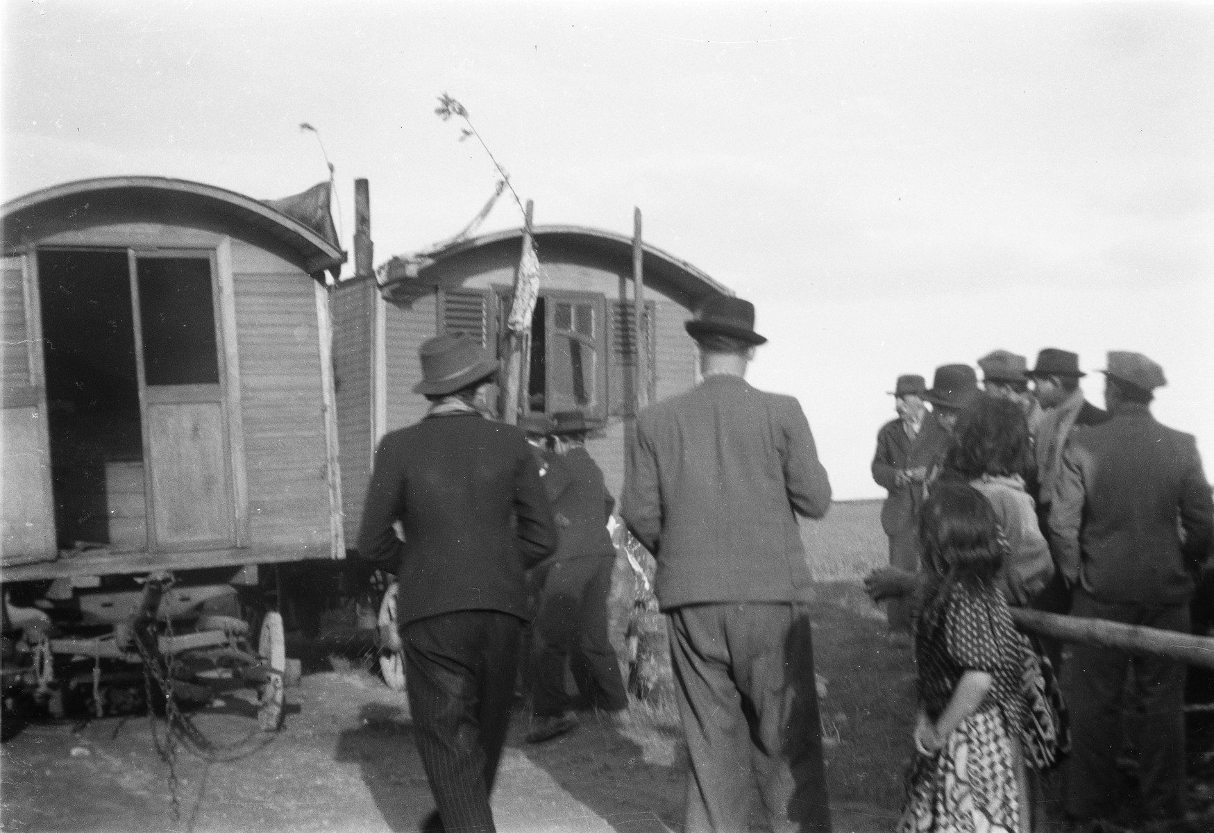 A group of Roma (Gypsies) gather around two caravans (possibly part of a celebration).