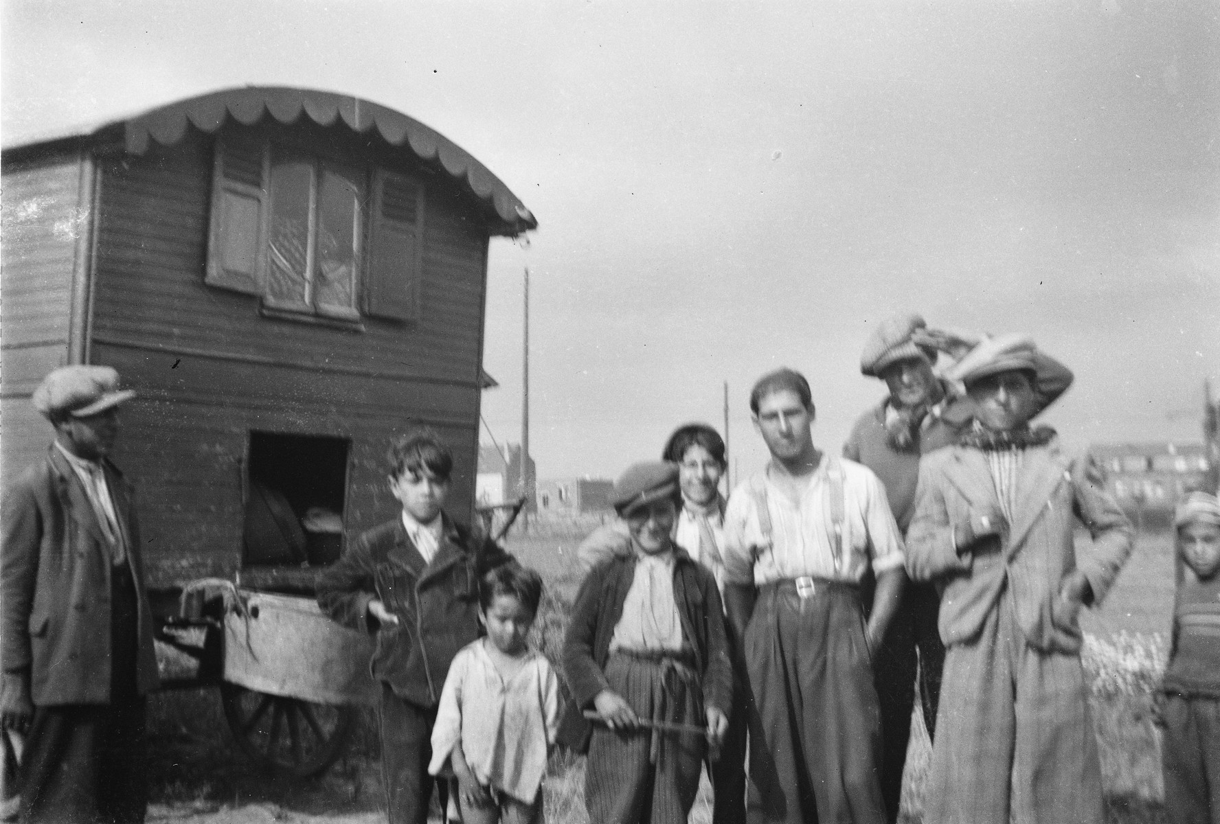 A group of Roma (Gypsy) men and boys poses by their caravan.