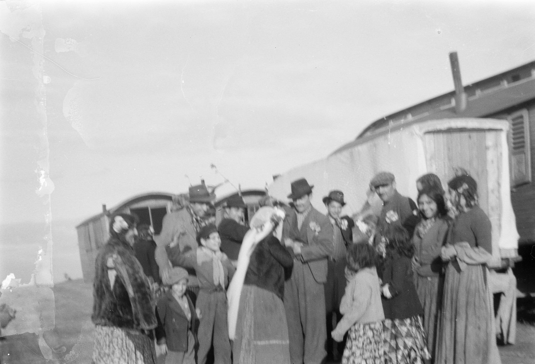A group of Roma (Gypsies) gathers around a couple during a celebration (possibly a wedding).