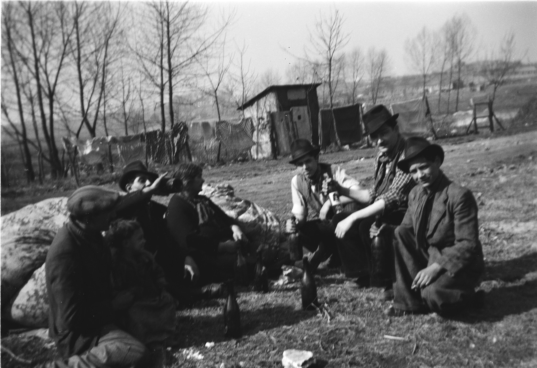 A group of Roma (Gypsy) men sit on the ground in a semi-circle, sharing a drink.