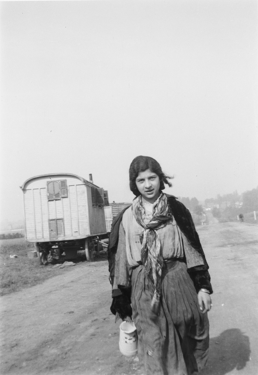 A young Romani (Gypsy) woman carrying a container walks down a road.