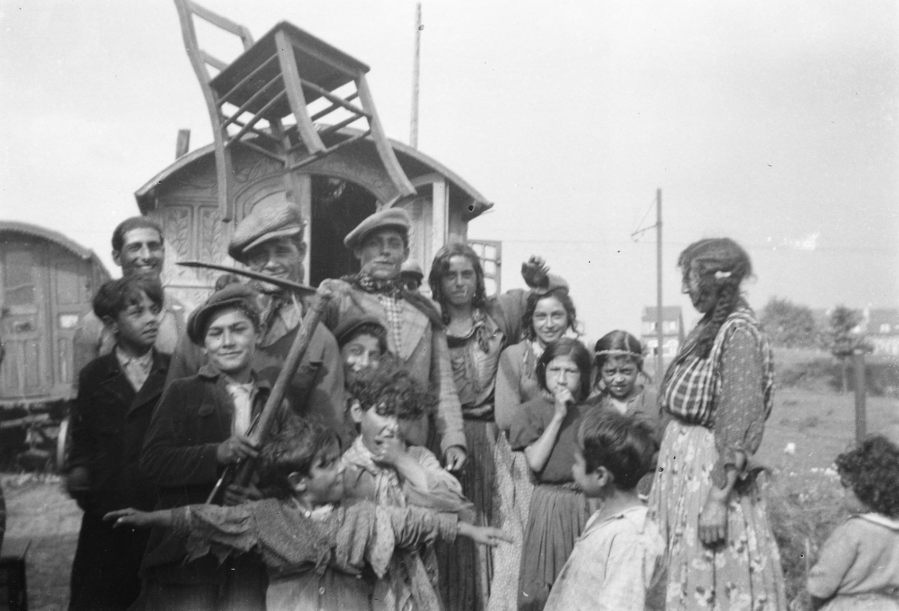 A group of Roma (Gypsies) in front of their caravan.  A child with arms outstretched playfully blocks the way, and a chair is balanced aloft above the group.