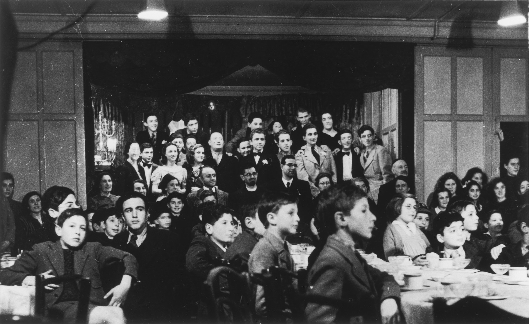 Jewish children from the Rowden Hall School attend a Hannukah party in an overflow hostel on Harold Road.  Among those pictured are Guenther Cahn, his brother Helmuth Cahn (later Harry Curtis, standing second row, fourth from right), Eric Hamburger (standing second row with a flower in his lapel), Kurt Berger ( standing, first row with glasses, a teacher recruited from the internees in the Kitchener Camp), Mr. and Mrs. Katz and Mrs. Bergel.