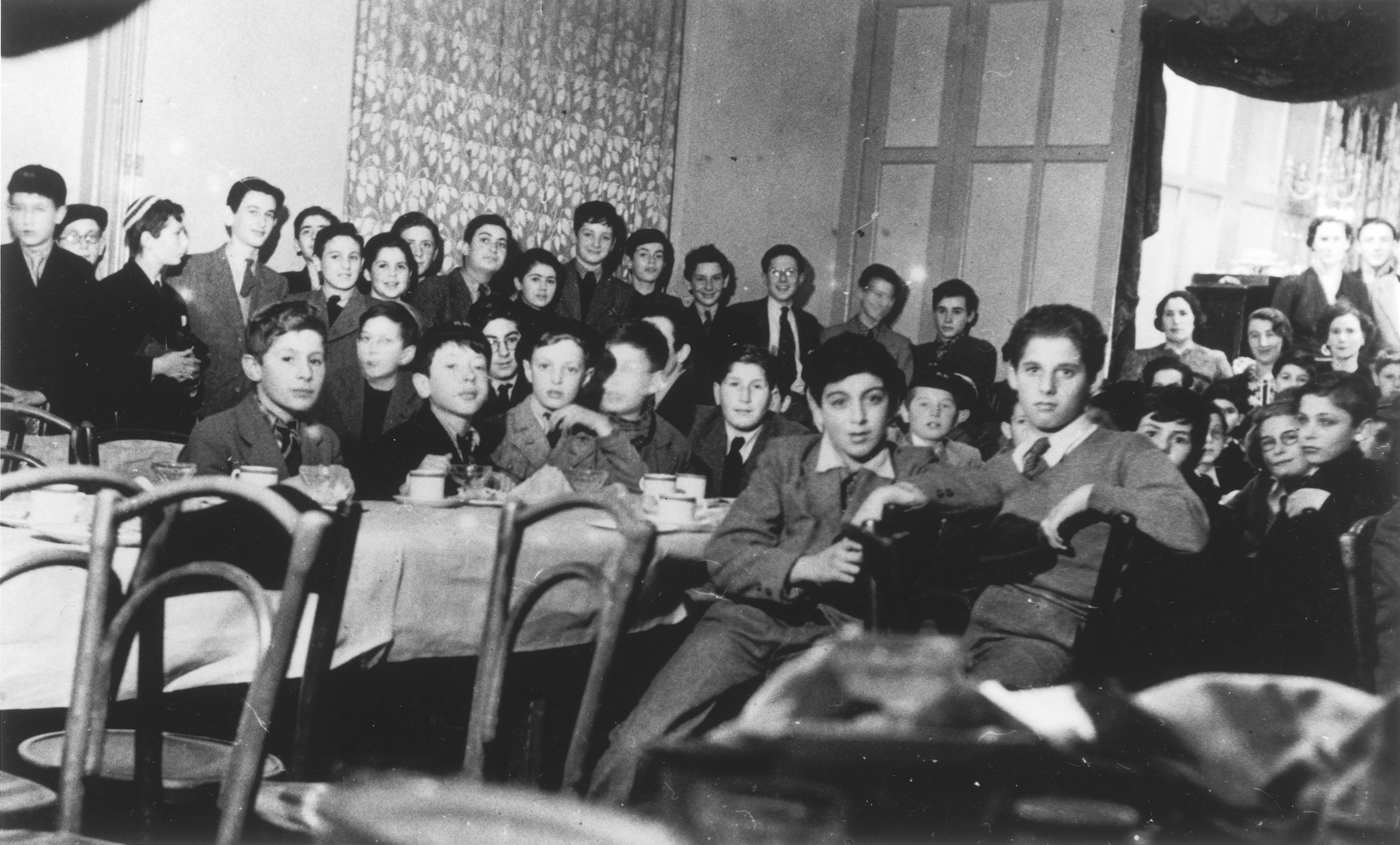 Jewish children from the Rowden Hall School attend a Hannukah party in an overflow hostel on Harold Road.  Among those pictured are Guenther Cahn, his brother Helmuth Cahn (later Harry Curtis), Eric Hamburger, Kurt Berger ( a teacher recruited from the internees in the Kitchener Camp), Mr. and Mrs. Katz and Mrs. Bergel. The third boy from the left sitting behind the table  with his hand  on his chin, is Fred Gottlieb.