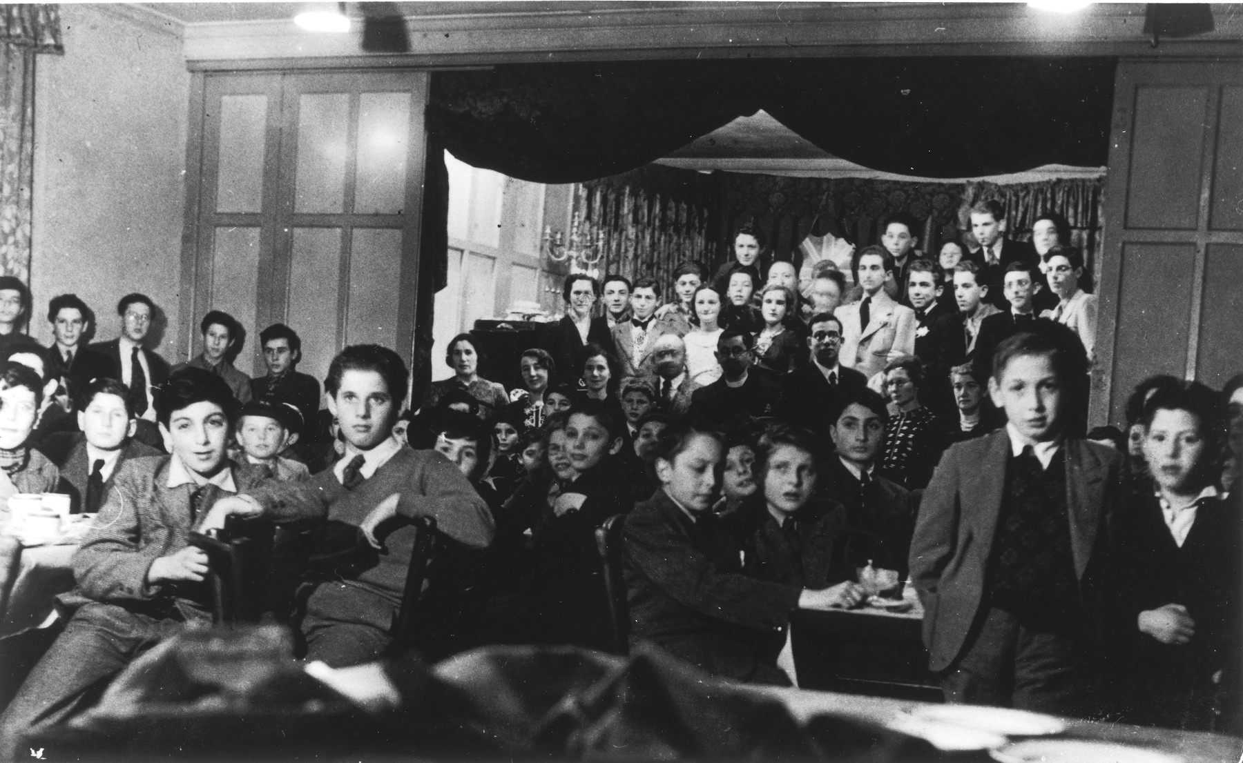 Jewish children from the Rowden Hall School attend a Hannukah party in an overflow hostel on Harold Road.  Among those pictured are Guenther Cahn, his brother Helmuth Cahn (later Harry Curtis), Eric Hamburger, Kurt Berger ( a teacher recruited from the internees in the Kitchener Camp), Mr. and Mrs. Katz and Mrs. Bergel.