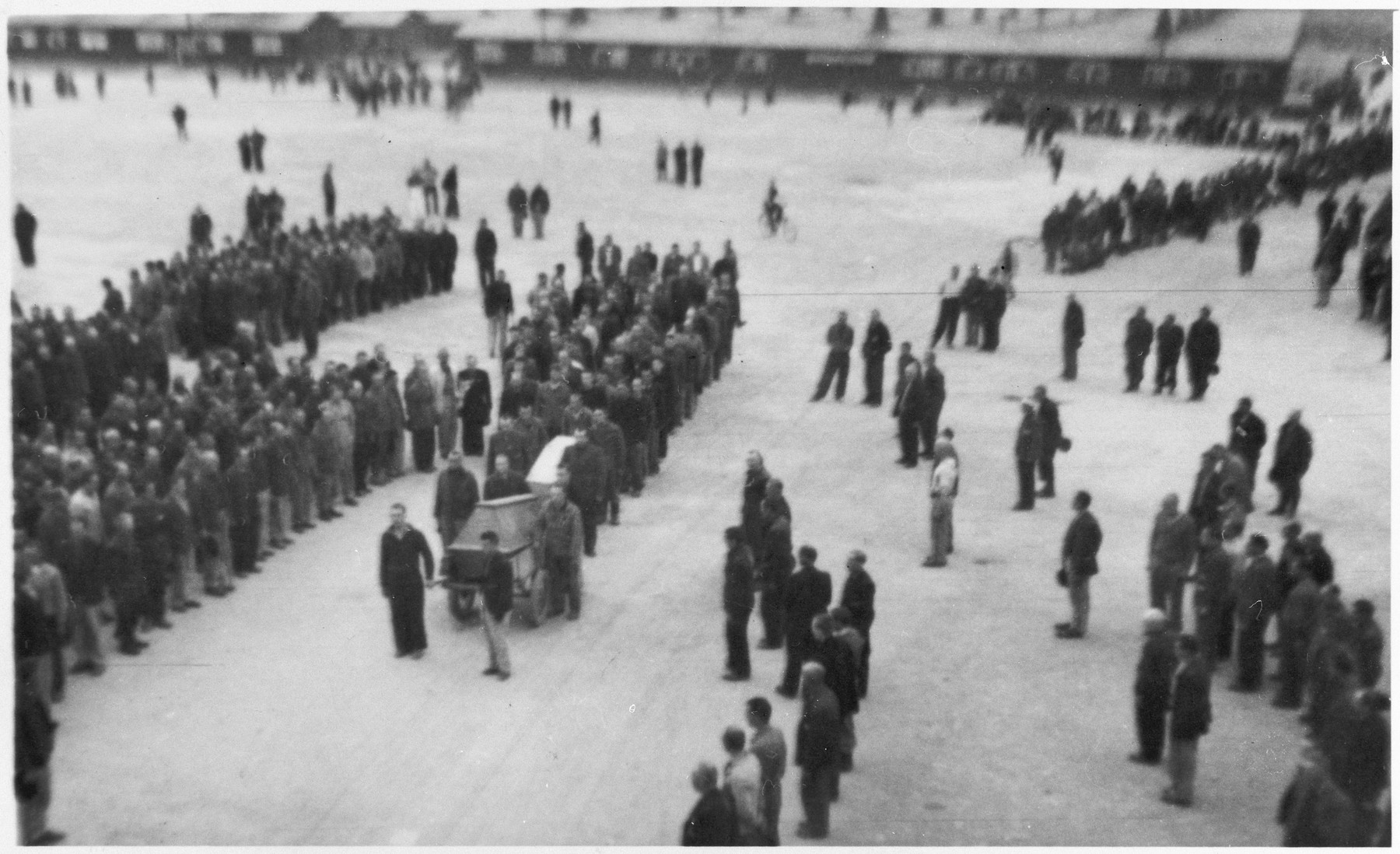 "Survivors gather in Buchenwald's main courtyard for the first burial procession at the camp.  Orignial caption reads: ""The first burial procession held at Buchenwald's main courtyard."""