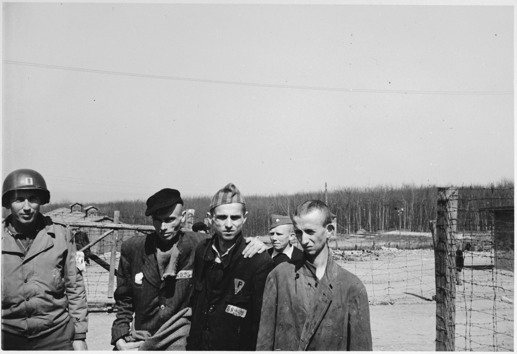 "Four survivors pose with an American soldier following the liberation of Buchenwald.  The original caption reads ""The expression on the prisoners' faces show their lack of emotion and interest in life."""