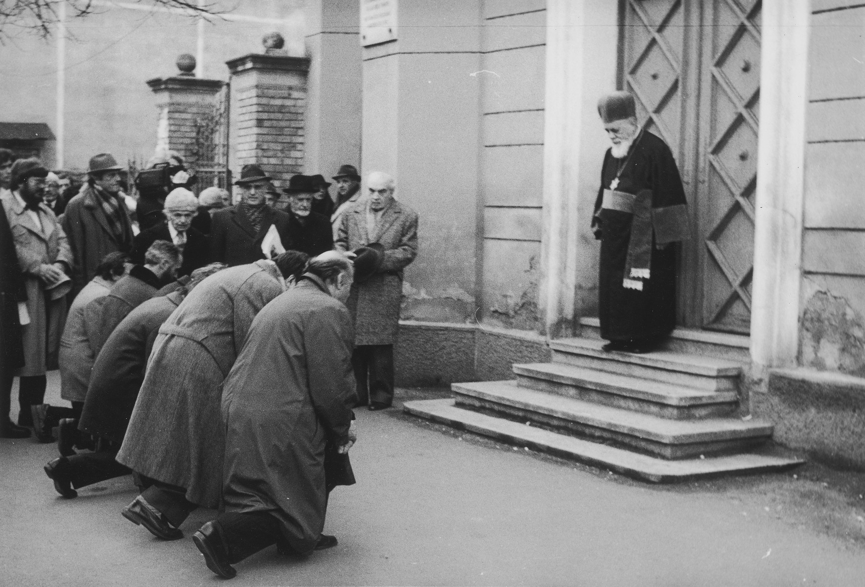 """In front of the """"Synagogue of the Deportation"""" in Cluj and in the presence of Romanian Chief Rabbi Moses Rosen (1912-  ), six Hungarian members of the Romanian Parliament ask for forgiveness for the sins of the Hungarian Fascists, for their cooperation in the extermination of more than 130,000 Jews from northern Transylvania.   They were deported to Auschwitz in 1944 by Adolf Eichmann, with the help of the Horthy-ites. Hungarian Bishop Tokes Laszlo takes part in this dramatic ceremony."""