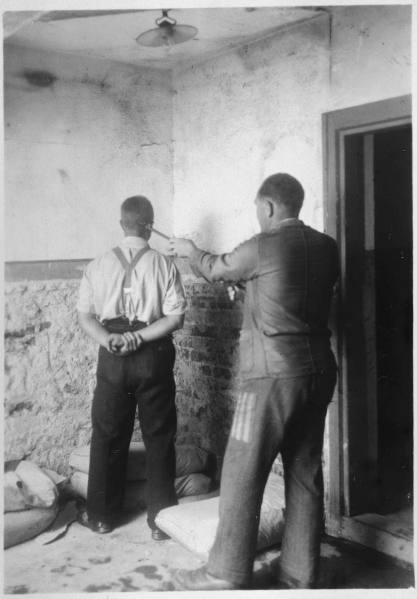 "Two survivors reenact an execution in the Mauthausen concentration camp.  Original caption reads: ""This is where they shot the refuges [sic], so the shots could not be heard outside, Camp Mauthausen. July 16, 1945."""
