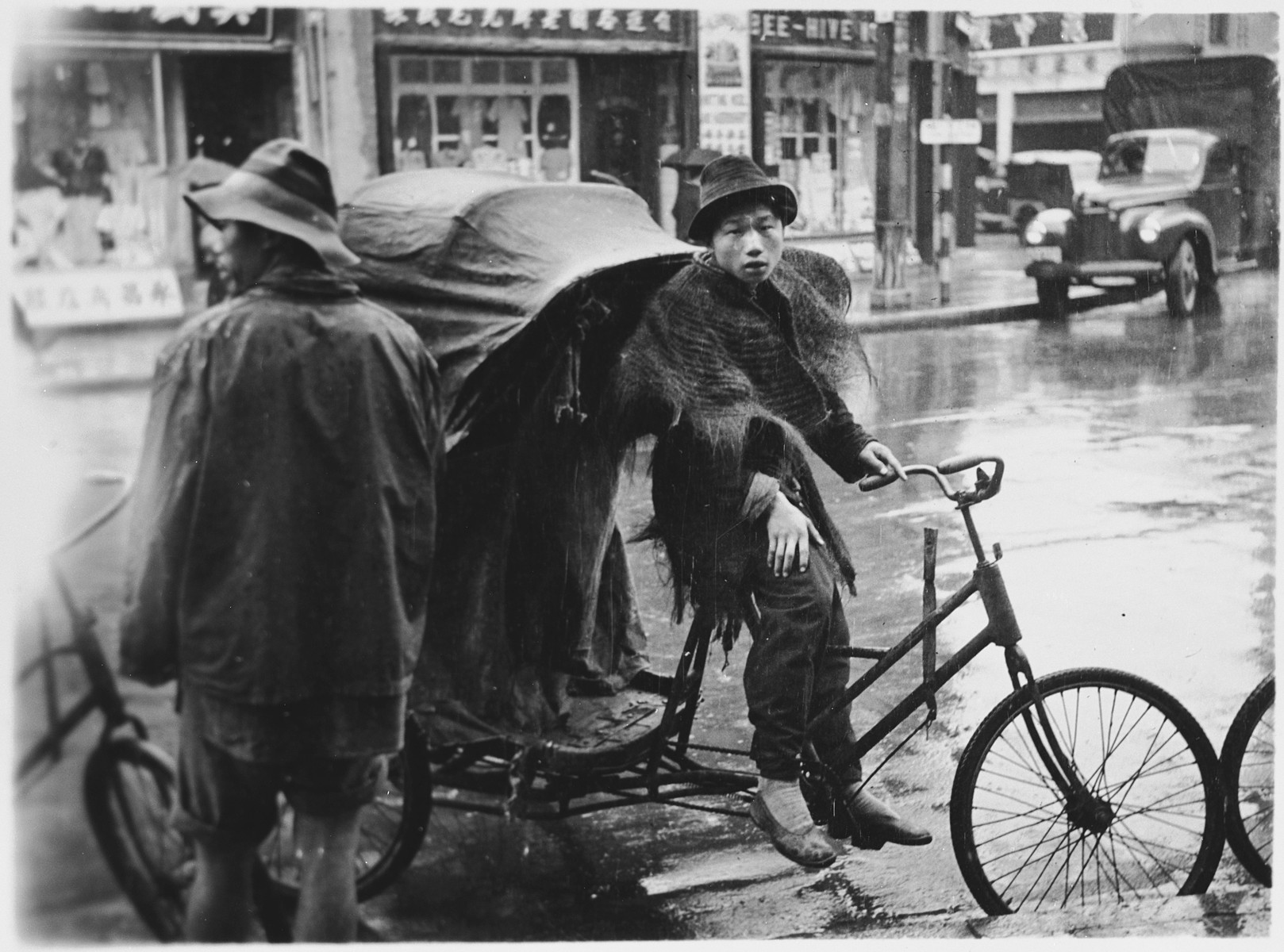 A Chinese youth seated on a bicycle cart.