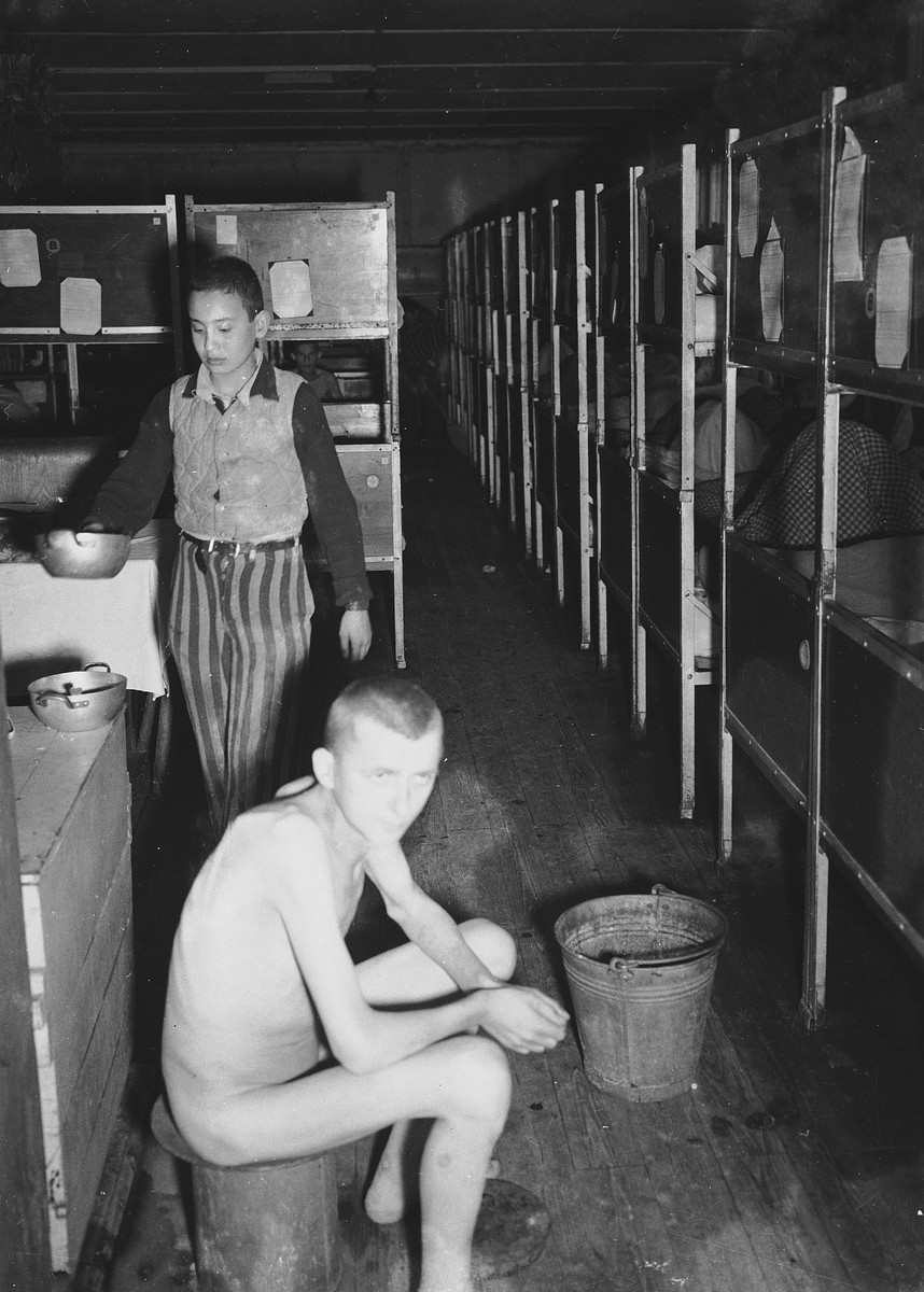 Close-up of two survivors, one naked, in an infirmary barracks of the Dachau concentration camp.