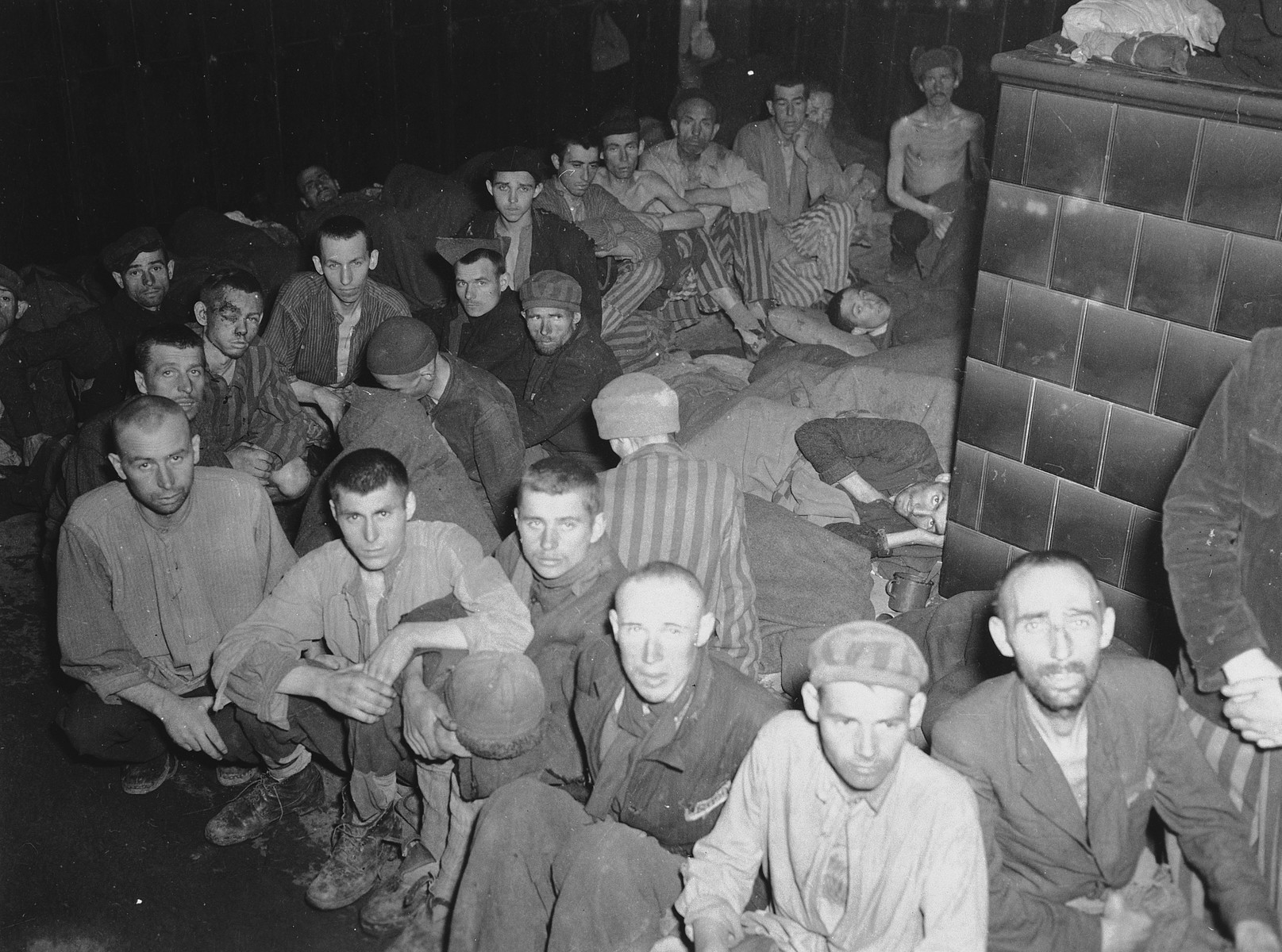 Survivors sit on the floor of a crowded barrack in the Dachau concentration camp.