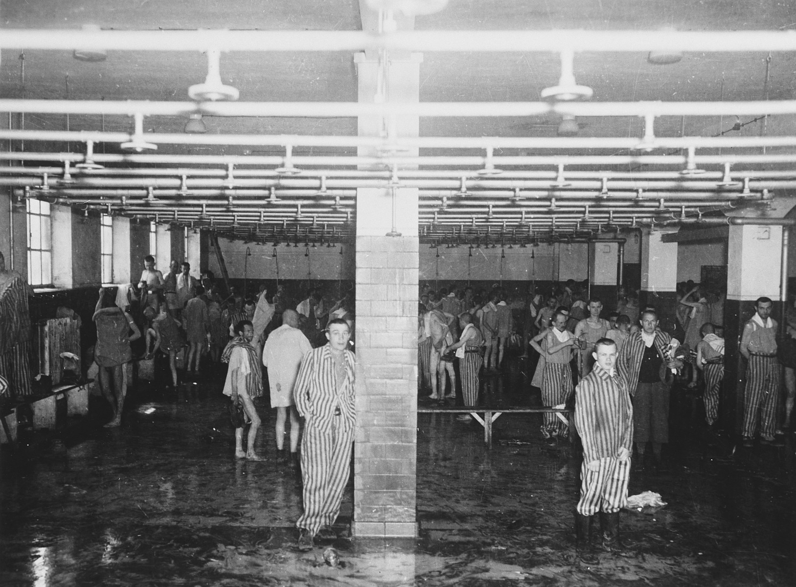 Survivors congregate in the Dachau shower barracks after liberation.