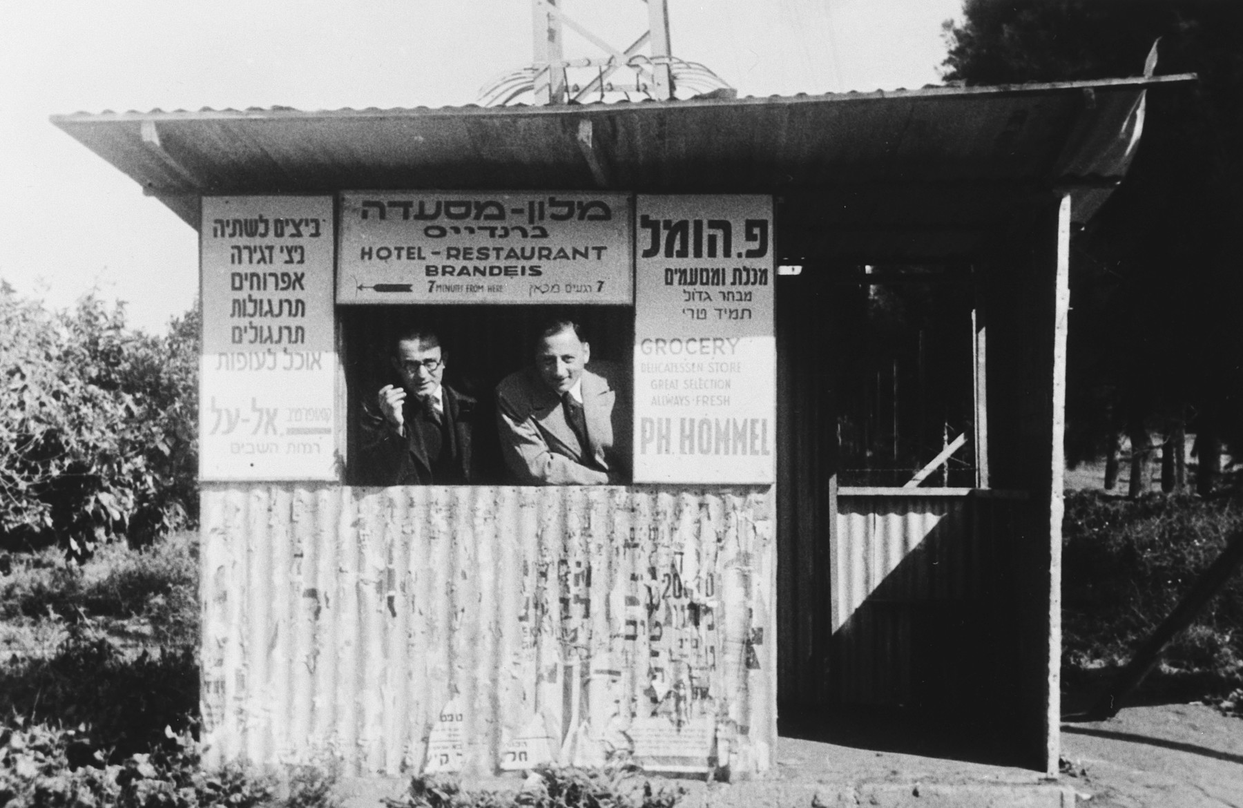 Two German Jews look out the window of a rustic foodbar entitled Hotel-Restaurant Brandeis.  Karl Blumenthal is pictured on the right.