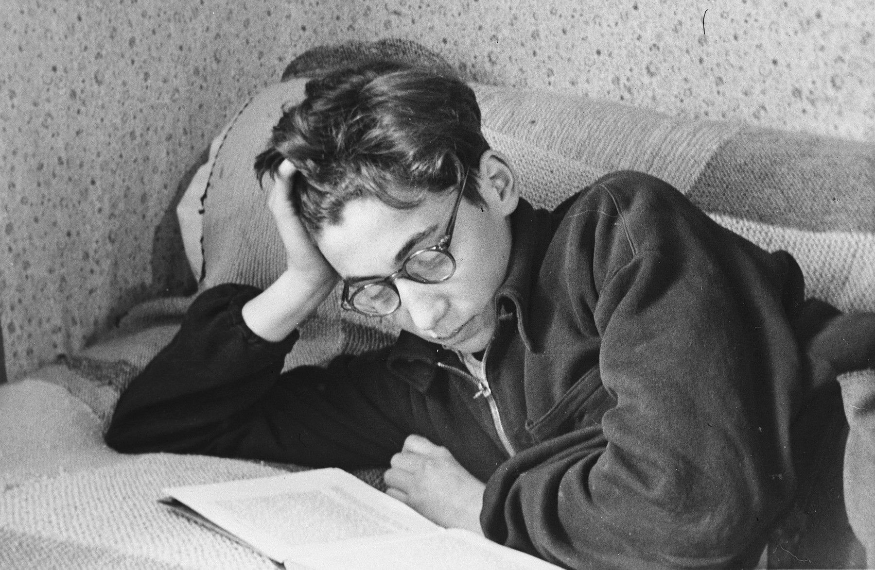 Close-up portrait of a teenage boy reading a book on his bed in a boarding school in Switzerland.  Pictured is a Hungarian survivor, Stefan Polgar, the donor's roommmate.