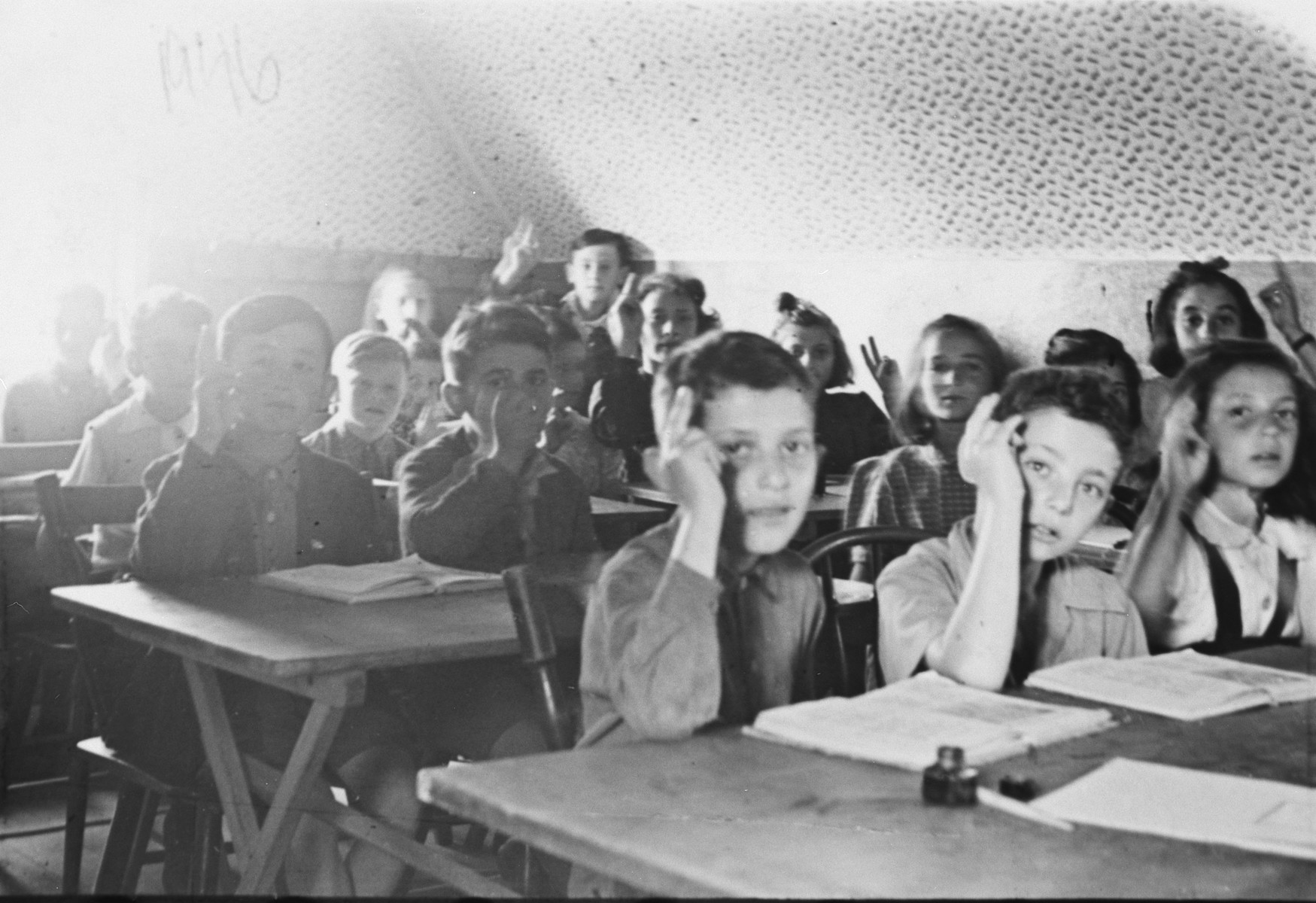 Children sit at their desks and raise their hands in a school in the Suttgart displaced persons' camp.  Lova Warszawczyk is pictured in the second row, on the left.