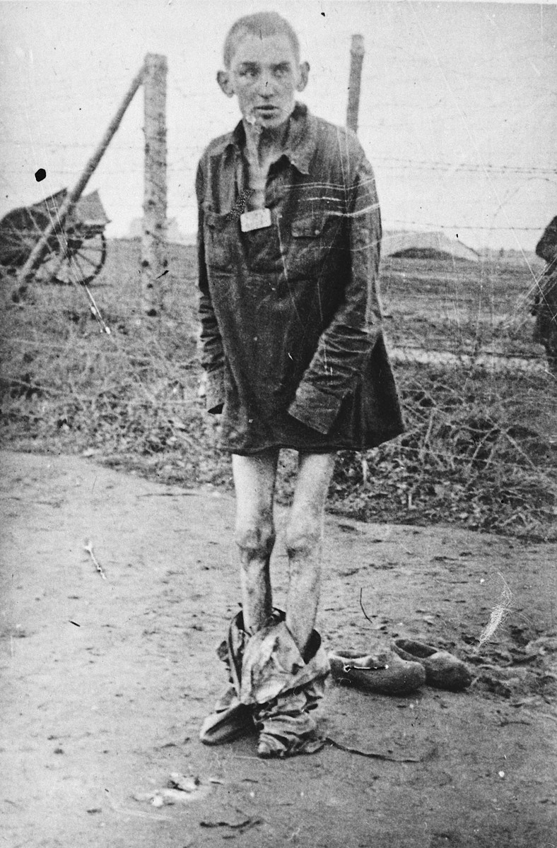 Close-up portrait of an emaciated survivor wearing only the shirt of his uniform [probably in the Nordhausen concentration camp].