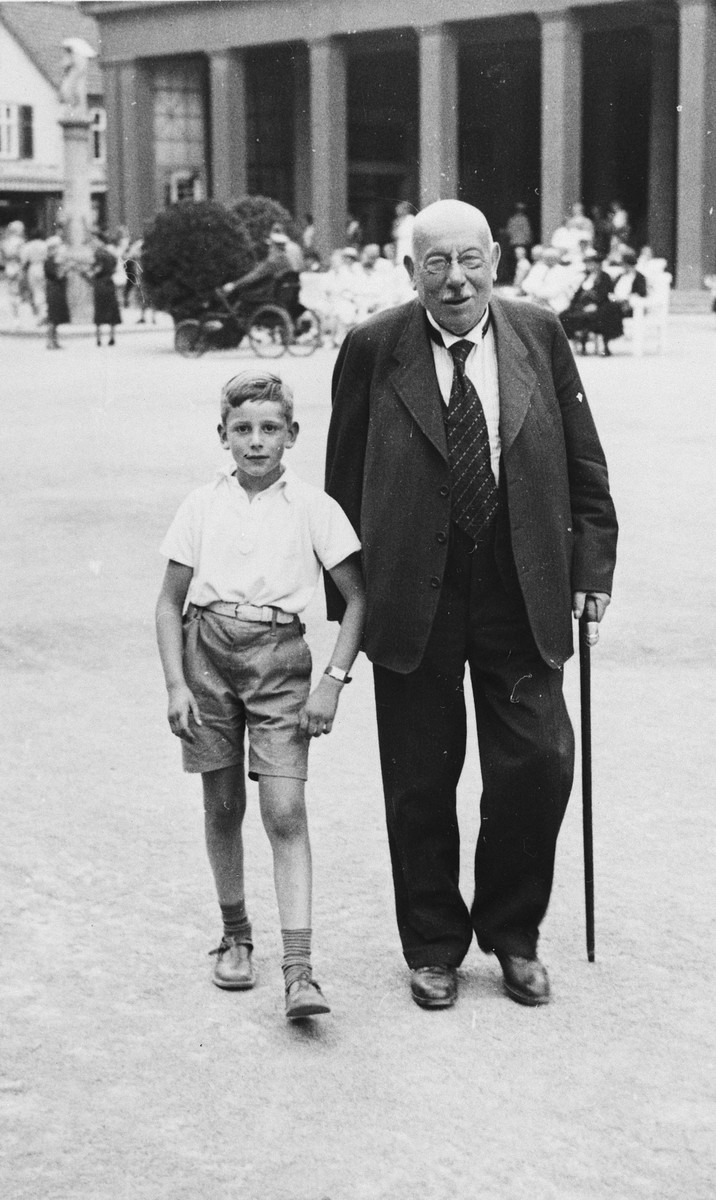 A grandfather walks through a public square with his grandson.  Pictured are Rolf Blumenthal and his paternal grandfather Julius Bumenthal.
