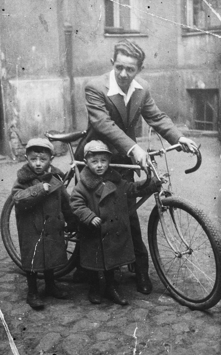 A young Polish-Jewish father stands next to his bicycle and his twin sons.  The father Eli Warszawczyk is the uncle of the donor.  The twins are  Froyke and Nechomke.  All subsequently perished in the Holocaust.