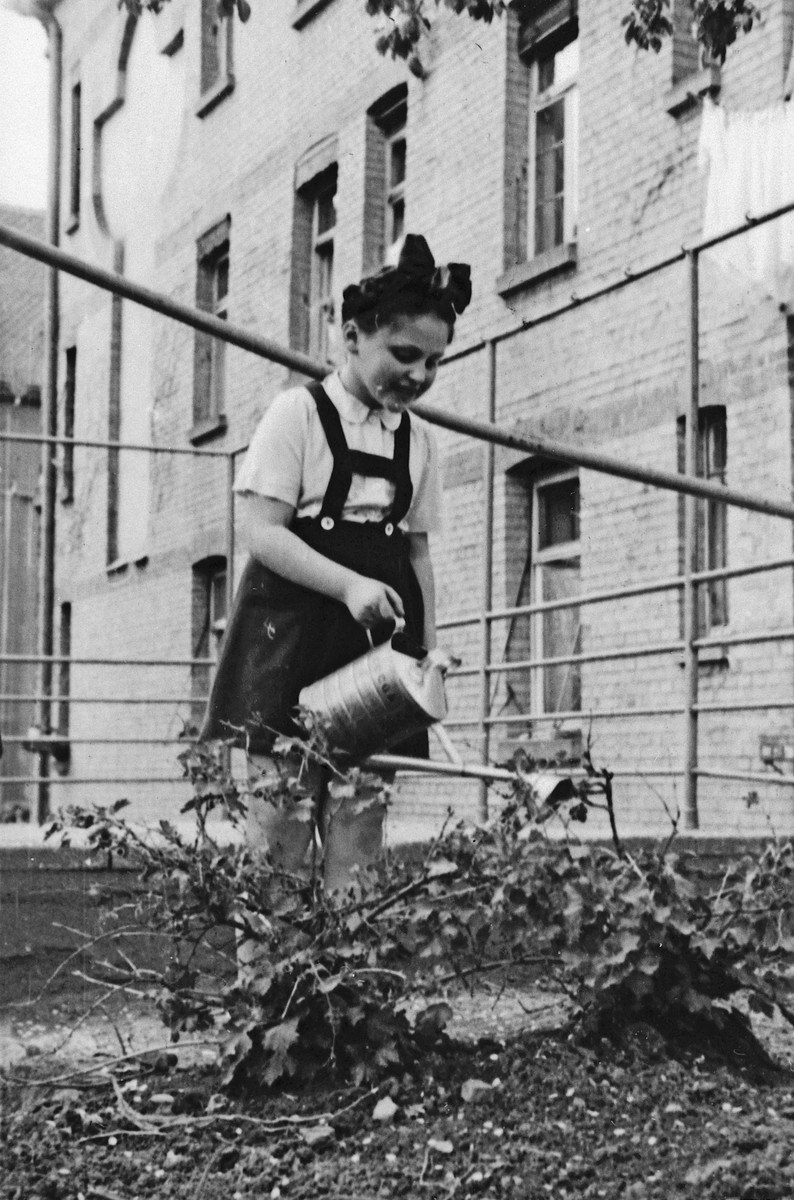 A young girl waters her garden in the Stuttgart displaced person's camp.  Pictured is Hadasa Gassenbauer.