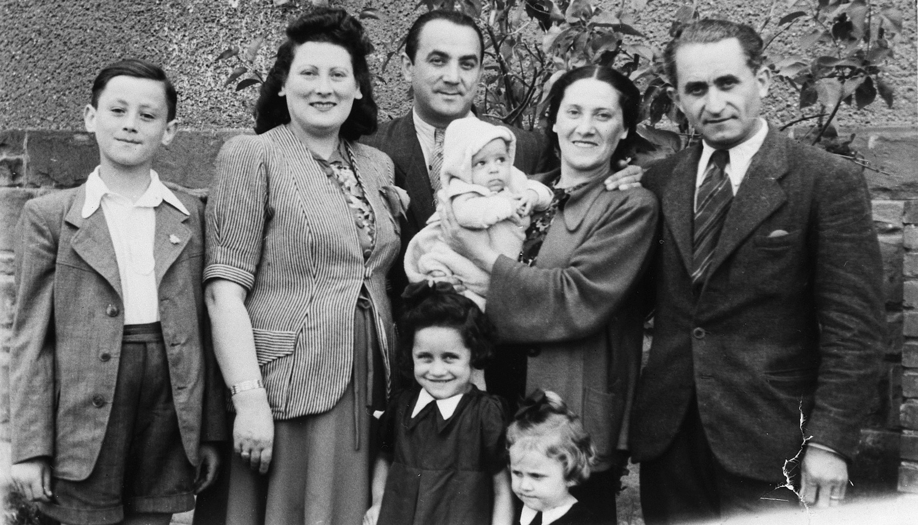 Portrait of an extended Jewish family in the Stuttgart displaced person's camp.  Pictured from left to right are Lova Warszawczyk and his parents, Masha and Josef Warszawczyk, Josef's brother Nathan Warszawczyk, his wife Chana holding her baby Baruch, and daughters Mira and Zilla .